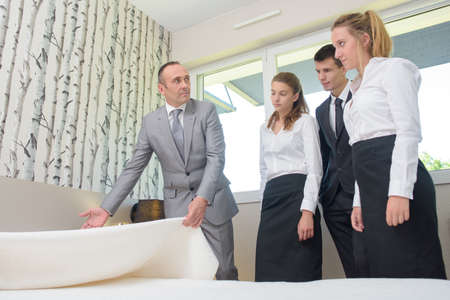 bedspread: Man with hotel staff, holding bedspread