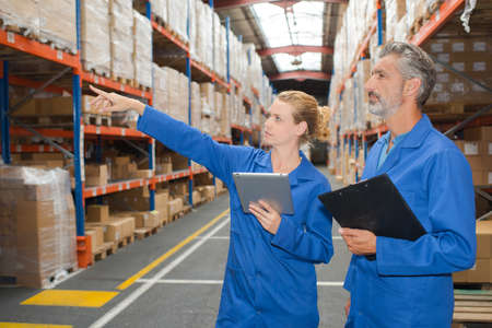senior men: Man and woman in warehouse, pointing to shelf
