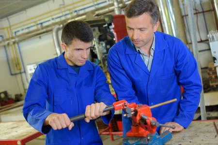 metalworker: Apprentice learning to use machinery Stock Photo
