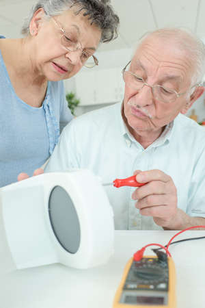 electrics: elderly man fixing a coffee machine