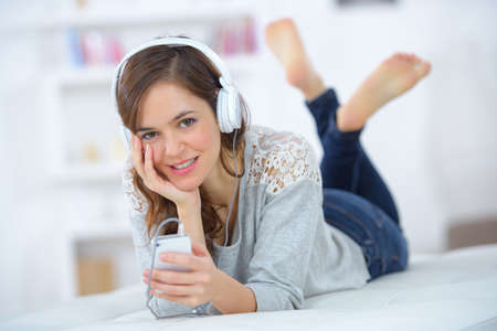 mp3: Lady layed on front, listening to mp3 player