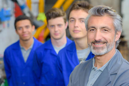 stood: Portrait of teacher stood in front of his three apprentices Stock Photo