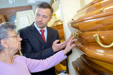 Señora mayor con el ataúd director de la funeraria elegir