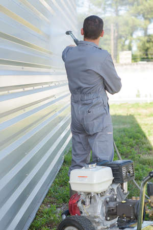 man power: Man power washing the side of a building