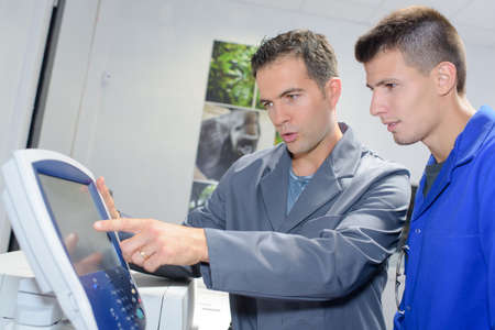 explaining: Man explaining controls of machine to apprentice