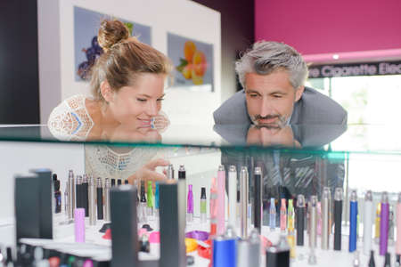 atomiser: Man and lady gazing into counter of vaporisers Stock Photo