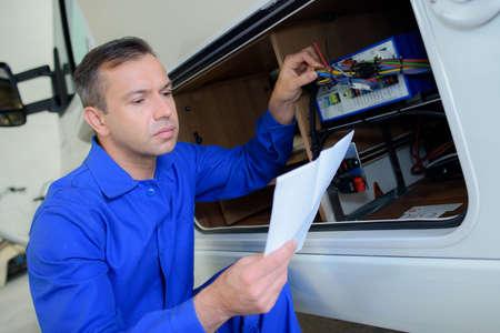 electrics: Mechanic checking electrics on campervan