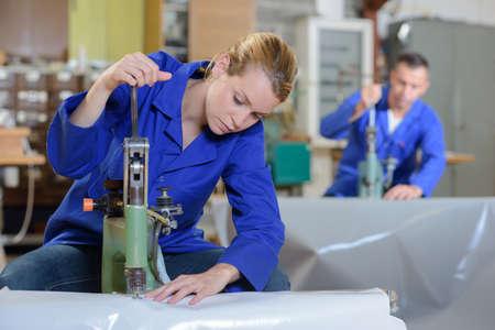 sheeting: Woman sewing through plastic sheeting