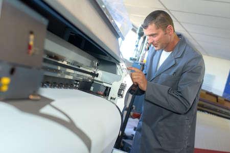 Man setting up printing machine Stock Photo