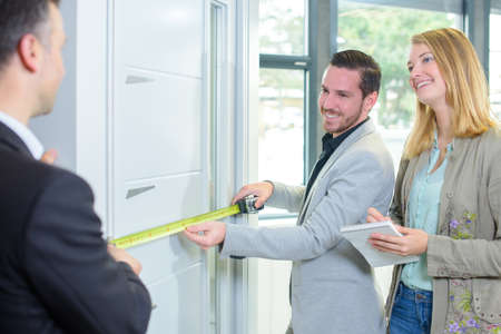 suitability: Couple measuring a door, salesman helping Stock Photo