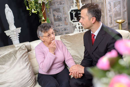 bereaved: Elderly lady in chapel of rest with suited young man