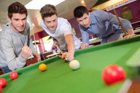 billiards tables: three young male in a billiard session