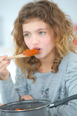 food testing: Young girl testing food from spoon Stock Photo