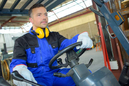 wheel loader: Man driving a forklift Stock Photo