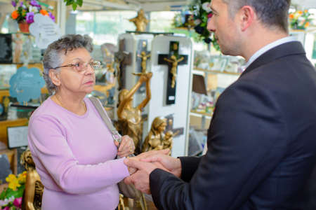 bereaved: Woman with undertaker amongst memorial artefacts