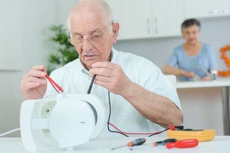electrical appliance: Elderly man using multi meter on electrical appliance