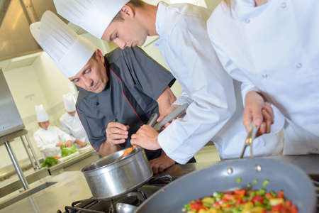 trainees: Chef checking trainees pan of food