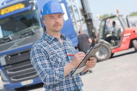 l'uomo in possesso di un appunti con il suo camion in background