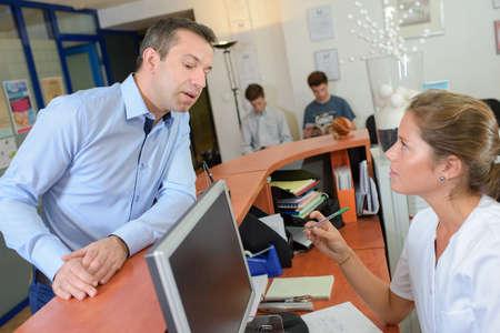 waiting glance: Man at reception desk glancing at computer screen Stock Photo