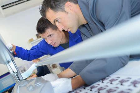 hombres trabajando: Dos hombres Configuración de la máquina de impresión profesional