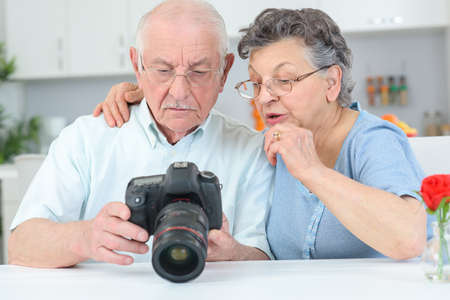couples hug: Elderly couple reviewing photos on display on digital camera