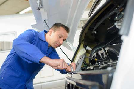 Mechanik pracuje nad przodu samochodu campingowego