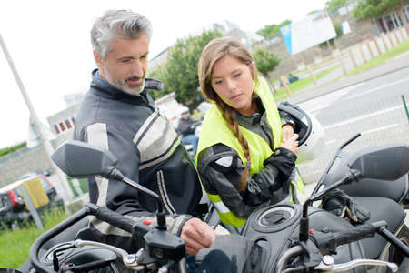 MOTORCYCLES: Young lady looking at motorcycle with older man