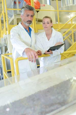 bata blanca: El hombre y la mujer de pie en un pasillo observando fábrica