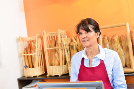 to till: Woman working on the till in a bakery