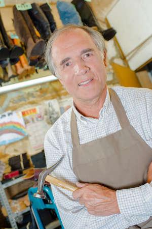 cobbler: Cobbler holding hammer Stock Photo
