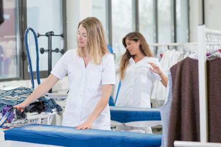 dry cleaners: Two ladies working in a dry cleaners Stock Photo