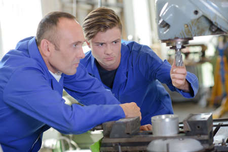 boron: Two workers looking at drill bit on industrial machine
