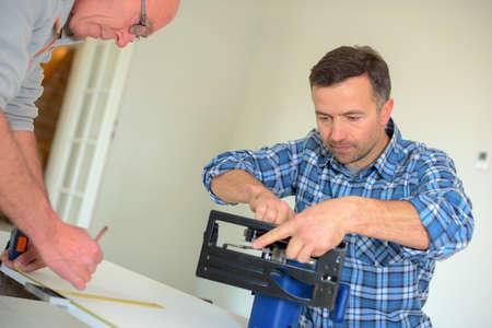 circular saw: Carpenter setting up a circular saw Stock Photo