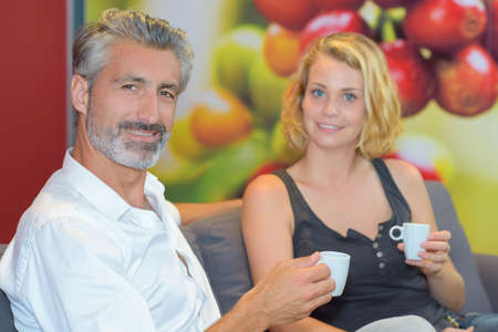 couple on couch: Couple sat on couch holding cup of drink
