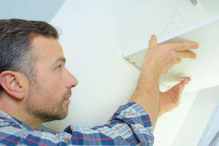 refurbish: Fitting kitchen storage unit Stock Photo