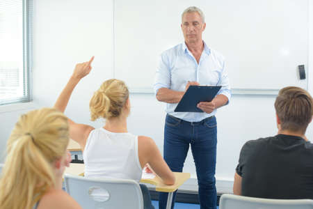female hands: Teacher in front of class, student with arm raised