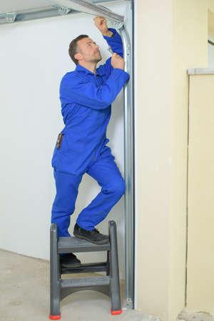 Hombre que repara el marco de una puerta de garaje