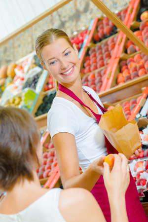 shop assistant: Shop assistant passing orange