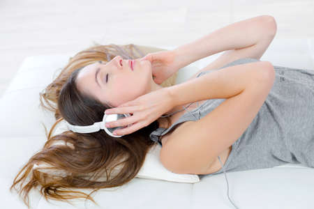 whilst: Listening to music whilst laying on the sofa Stock Photo