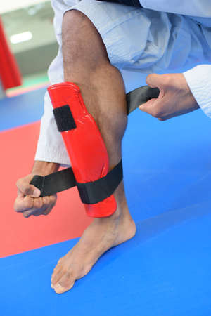 martial artist: Martial artist attaching leg guard Stock Photo