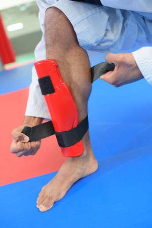 stance: Martial artist attaching leg guard Stock Photo