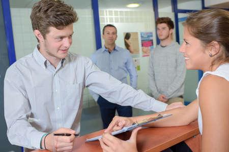 secretary desk: signing up for registration Stock Photo