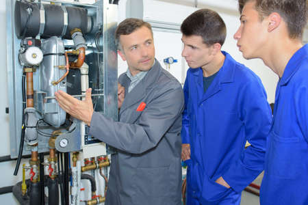 Man presenting boiler to apprentices Stock Photo