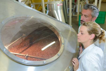 vat: Man and woman looking through porthole of vat