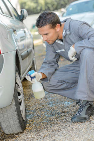 impact wrench: Mechanic cleaning a tyre Stock Photo