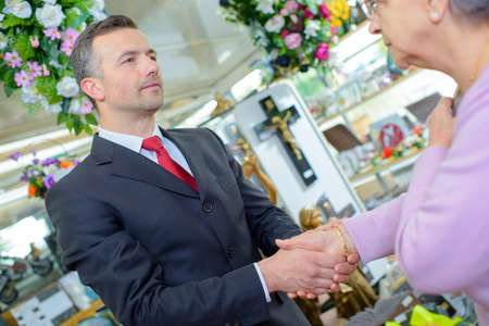 bereaved: Funeral director shaking hands with elderly woman