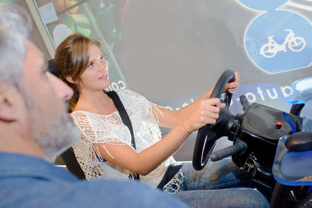 observed: Lady on driving simulator being observed by man Stock Photo