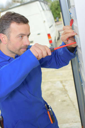 manual measuring instrument: Using a screwdriver on a fusebox