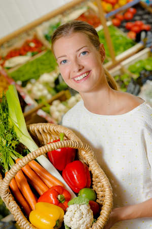 grocers: lady holding basket of mixed vegetables