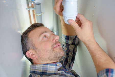 tightly: Making sure a pipe is tightly sealed Stock Photo